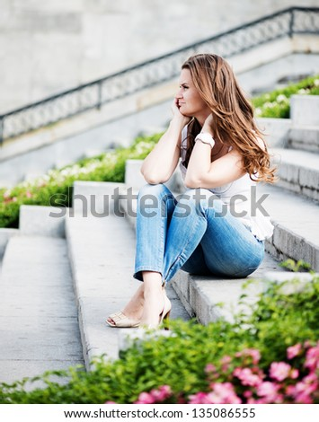 Portrait of a beautiful european woman sitting om steps - stock photo