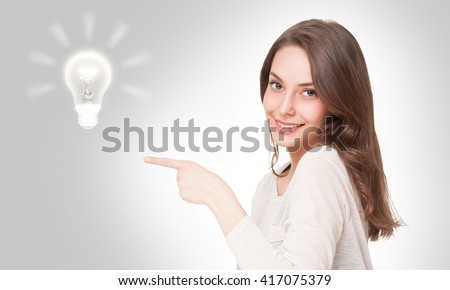 Portrait of a beautiful expressive young brunette with light bulb idea sign.