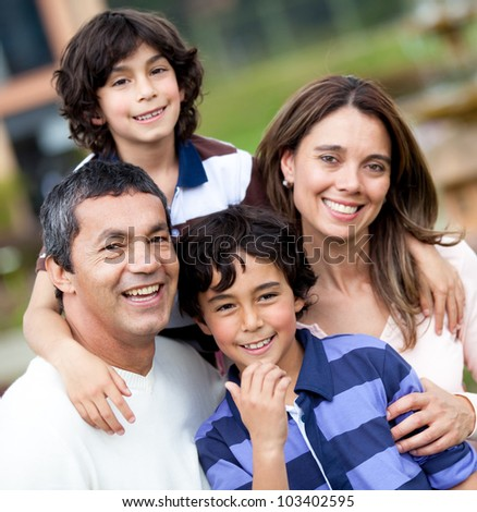 Portrait of a beautiful family smiling and looking happy - outdoors - stock photo