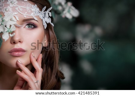 Portrait of a beautiful fashion bride wedding dress , sweet and sensual . Wedding makeup and hair . Flowers background. Art in a contemporary style Against the background of blooming apple orchards . - stock photo