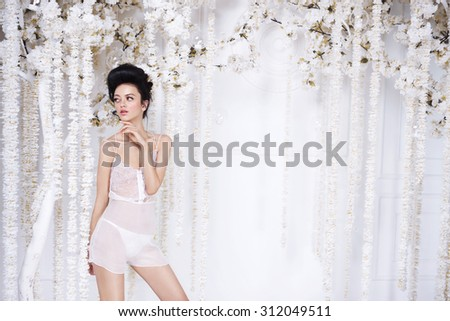 Portrait of a beautiful fashion girl in lingerie, sweet and sensual. Wedding make up and hair. Flowers background. Art modern style. Blue eyes - stock photo