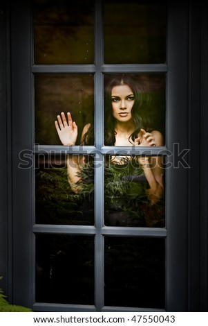 portrait of a beautiful fashion looking out the window - stock photo