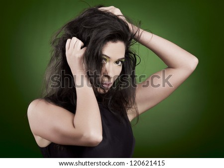 Portrait of a beautiful fashion woman over a green background