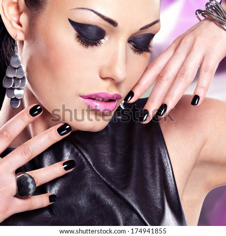 Portrait of a beautiful  fashion woman with black nails and bright makeup.  Pretty sexy face of a glamour girl posing at studio over art color background