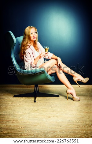 Portrait of a beautiful fashionable model sitting in a chair in Art Nouveau style. Interior, furniture. - stock photo