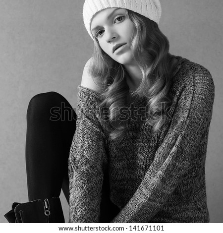 Portrait of a beautiful fashionable model with long curly hair in white hat posing over gray background. Studio shot. Daylight - stock photo