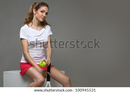 portrait of a beautiful female athletes with a tennis racket and the tennis ball in her hands - stock photo