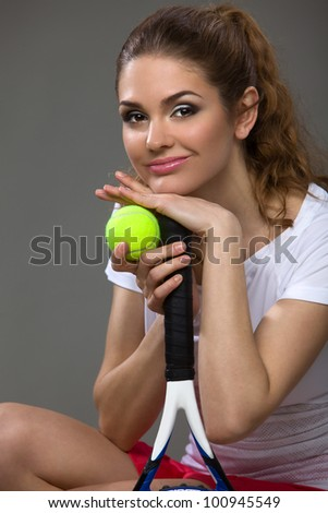 portrait of a beautiful female athletes with a tennis racket and the tennis ball in his hands - stock photo