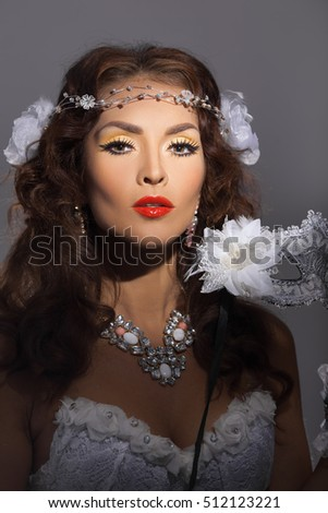 Portrait of a beautiful female model in a snowy white mask against gray studio background looking at camera. Christmas Holidays Party.
