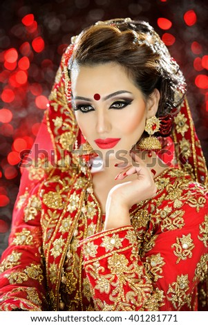 Portrait of a beautiful female model in traditional ethinic indian costume with jewellery and heavy makeup in a bridal style - stock photo