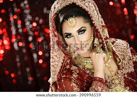 Portrait of a Beautiful Female Model in Traditional Indian Asian Bridal Wedding costume with makeup and jewellery