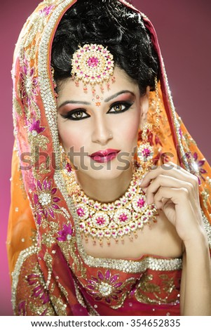 Portrait of a beautiful female model in traditional indian bride outfit with makeup and jewellery