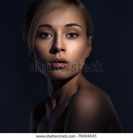 Portrait of a beautiful female model on dark background - stock photo