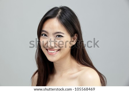 Portrait of a beautiful female model on isolated gray background - stock photo