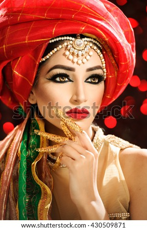 Portrait of a beautiful female model wearing a turban and ethnic jewellery on the head looking exotic - stock photo