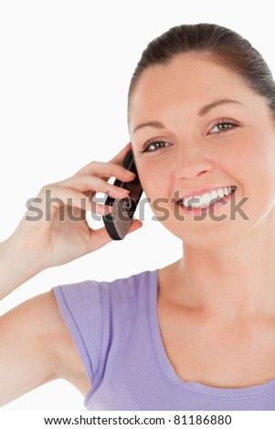 Portrait of a beautiful female on the phone while standing against a white background