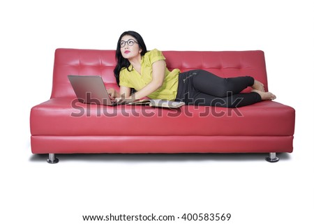 Portrait of a beautiful female student using laptop computer while reading a book and imagine something - stock photo