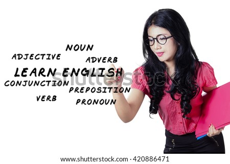 Portrait of a beautiful female teacher with long hair, writing english materials on the whiteboard - stock photo