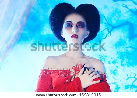 Portrait of a beautiful female vampire over moonlight background. - stock photo