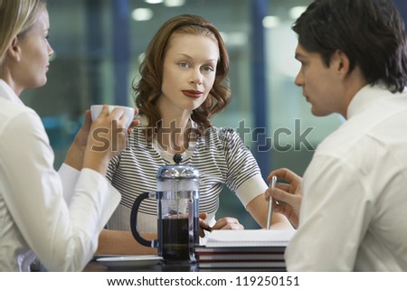 Portrait of a beautiful female with business colleagues in foreground