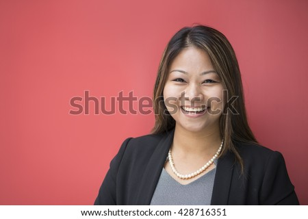 Portrait of a beautiful Filipino businesswoman in smart suit leaning against a red wall.  - stock photo