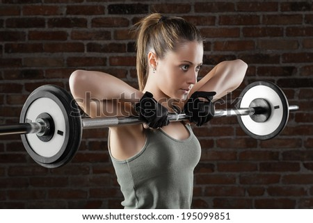 Portrait of a beautiful fit woman pushing up on brick background  - stock photo