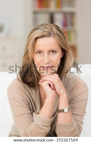 Portrait of a beautiful friendly middle-aged woman sitting on a couch at home resting her chin on her hands looking at the camera with a smile - stock photo