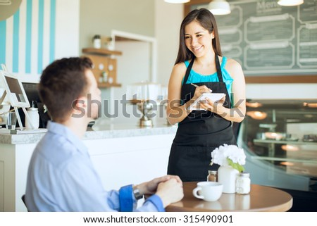 Portrait of a beautiful friendly waitress taking an order from a customer and writing it down on a notepad - stock photo