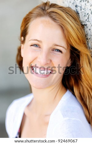 portrait of a beautiful ginger readhead outdoors with a big smile and friendly face - stock photo