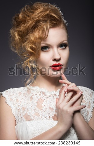 Portrait of a beautiful ginger woman with red lips in the image of the bride. Picture taken in the studio on a grey background. Beauty face - stock photo