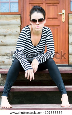 Portrait of a beautiful girl against a wooden house - stock photo