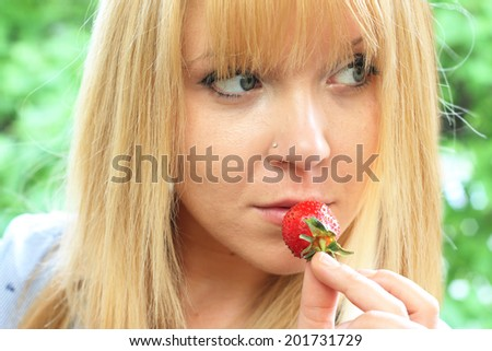 portrait of a beautiful girl eating a strawberry