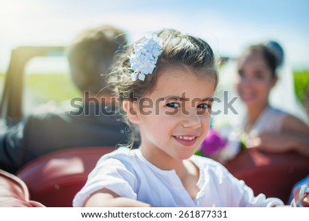 Portrait of a beautiful girl going at her parent's wedding at the back of a retro car. Focus on the face - stock photo