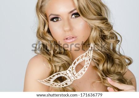 portrait of a beautiful girl holding a venetian mask - stock photo