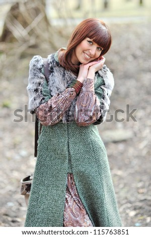 Portrait of a beautiful girl holding hands near the face outdoors - stock photo