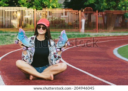 Portrait of a beautiful girl holding roller skates in her hand, sitting on the street, looking at camera and smiling. Outside - stock photo