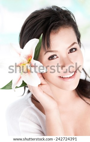 Portrait of a beautiful girl holding tropical flower in hand close to her face - copy space - stock photo