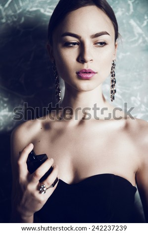 Portrait of a beautiful girl in a black dress with spirits in hands - stock photo