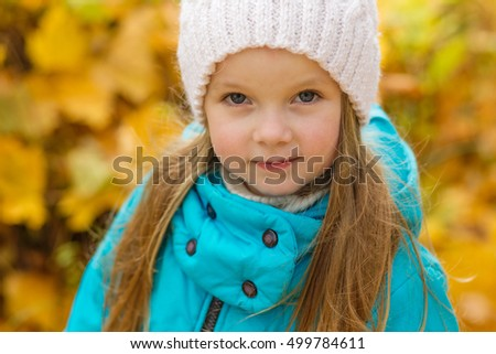 Portrait of a beautiful girl in a blue coat outdoors in autumn. Child in autumn park