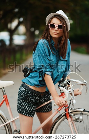 portrait of a beautiful girl in a hat and sunglasses with a bicycle in summer - stock photo
