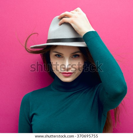 Portrait of a beautiful girl in a hat in the studio on a pink background - stock photo