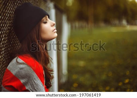 portrait of a beautiful girl in a hipster hat and striped jacket at the gate outdoor - stock photo