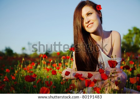 portrait of a beautiful girl in a poppy field at sunset - stock photo