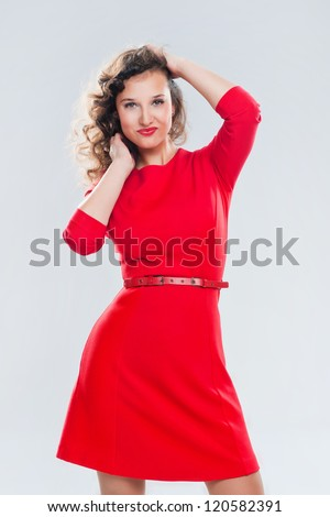 Portrait of a beautiful girl in a red dress on a gray background - stock photo