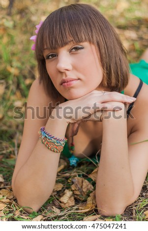 Portrait of a beautiful girl in green dress lying on the ground in autumn park