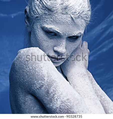 Portrait of a beautiful girl in the frost on his face on a blue ice background - stock photo