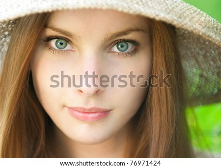 portrait of a beautiful girl in the hat on a green background - stock photo