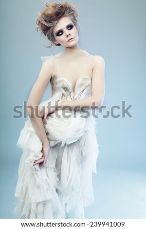 Portrait of a beautiful girl in the studio in a white dress