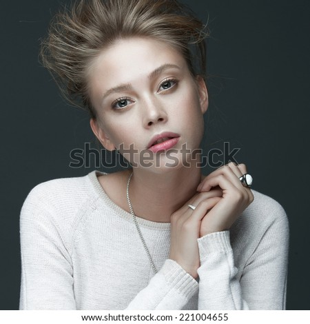 Portrait of a beautiful girl in white clothes posing in the studio on a gray background, the concept of beauty and health - stock photo