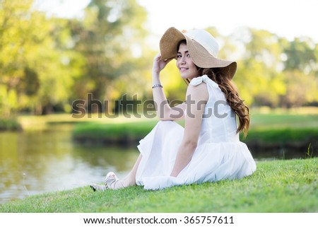Portrait of a beautiful girl in white dress, sitting on the grass field at the river side - stock photo